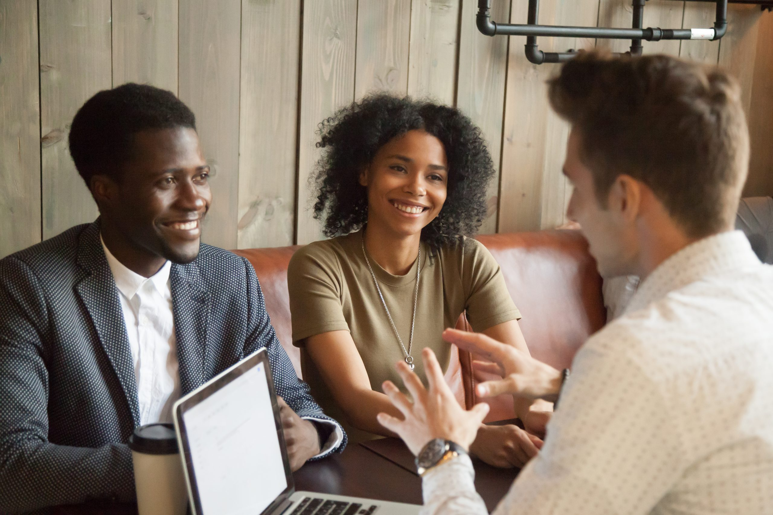 Caucasian architect talking to smiling African American couple, explaining housing project idea in coffee shop, male realtor consulting black clients on property purchase, having conversation in cafe